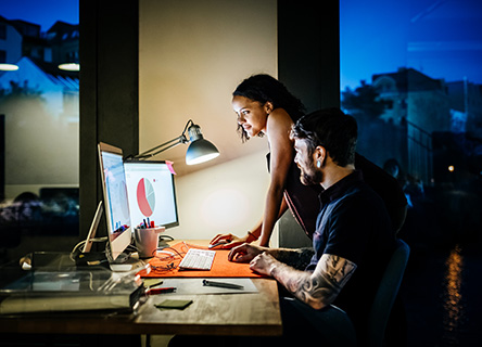 two college students working on a data group project at night