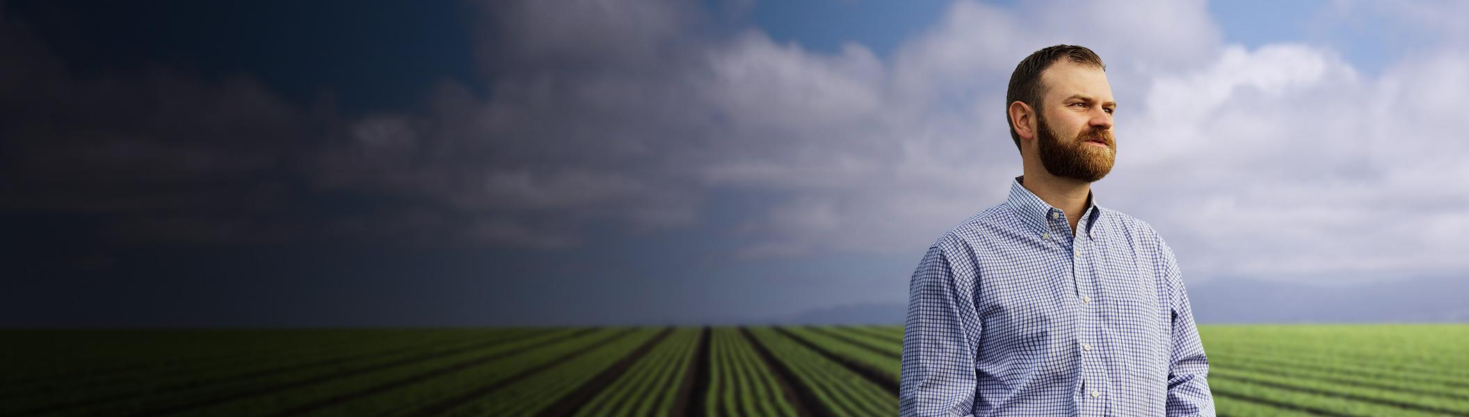 Homme dans une exploitation agricole qui regarde au loin