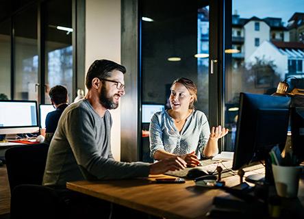 deux membres de l'équipe travaillant sur un projet de données dans la soirée