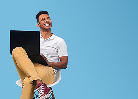 jeune homme assis avec un ordinateur portable et souriant