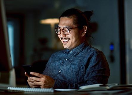 young man smiling at his phone screen