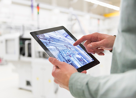 woman standing outside at night with her tabletman holding a tablet in a bright modern factory