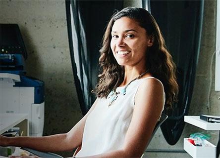 woman sitting at desk smiling