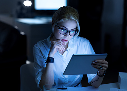 young woman testing new gadget at work in a dark office