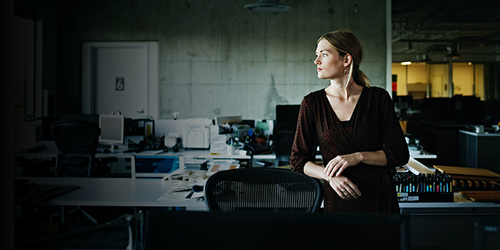 young businesswoman looking to her left in an empty office
