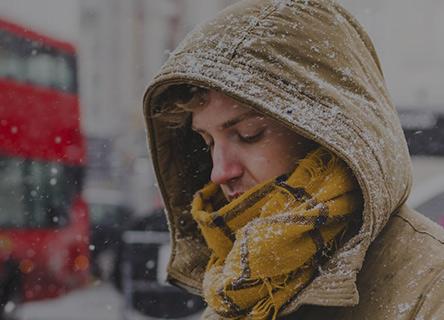 homme regardant son téléphone un jour de neige