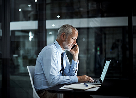 man working late at night in a modern glass office