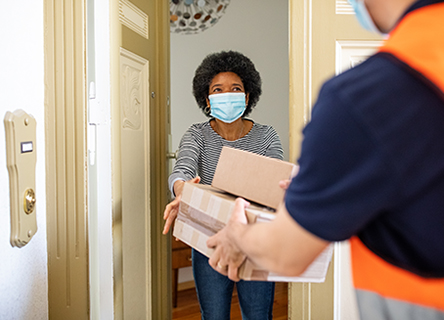 Woman getting package at door with mask on