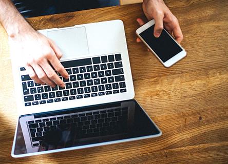 Man using laptop and phone at same time
