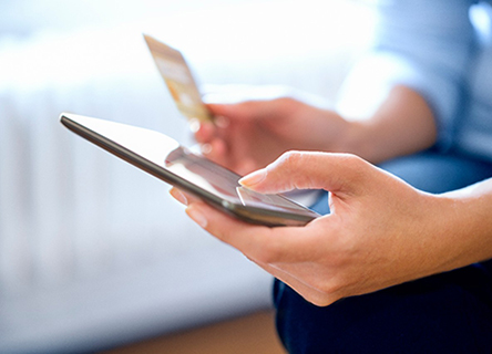 Woman with phone and credit card in hand